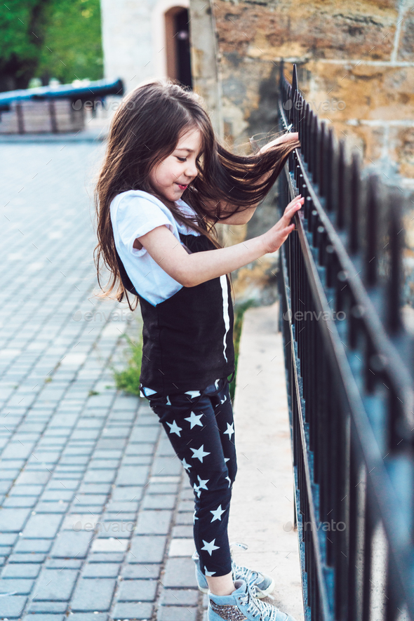 Little girl playing at fence - Stock Photo - Images