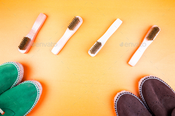 Green and brown suede espadrille shoes with brushes on yellow paper background. - Stock Photo - Images
