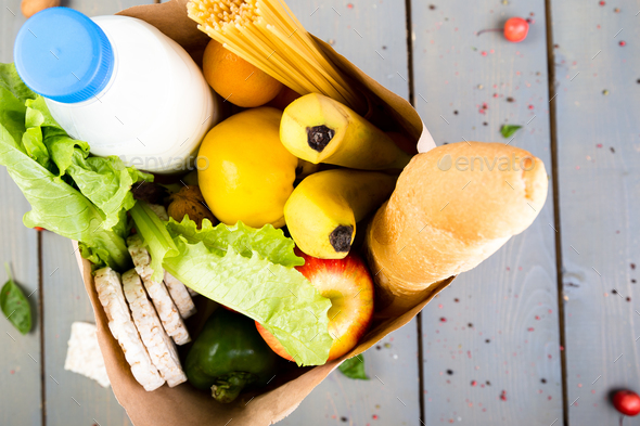 Grocery shopping concept. Different food in paper bag on wooden background.  Top view. - Stock Photo - Images