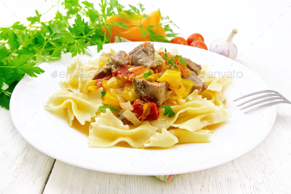 Farfalle with turkey and vegetables in sauce on board - Stock Photo - Images