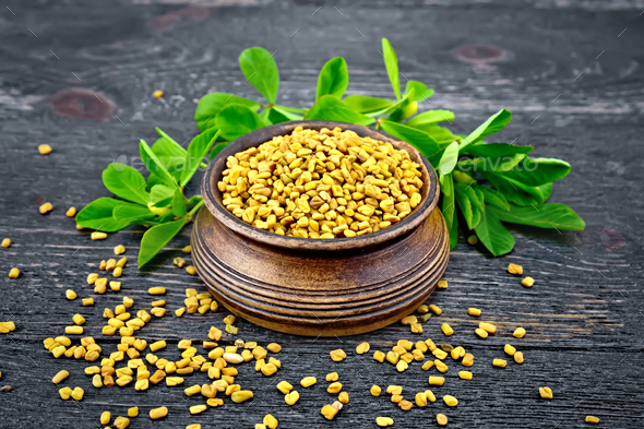 Fenugreek with leaf in bowl on wooden board - Stock Photo - Images
