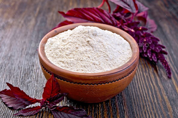 Flour amaranth in clay bowl with flower on dark board - Stock Photo - Images