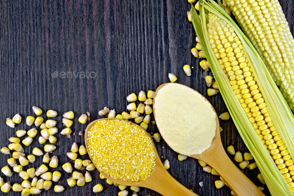 Flour and grits corn in spoons on wooden board - Stock Photo - Images