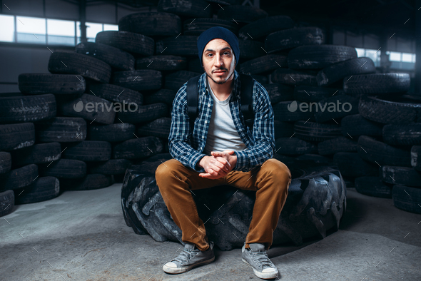 Stalker, alone traveler against mountain of tires - Stock Photo - Images
