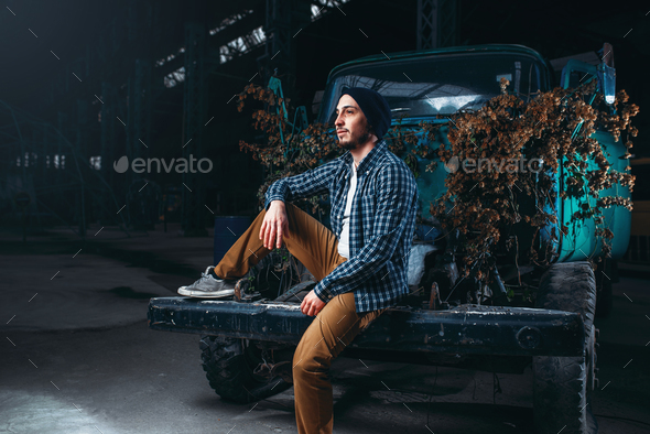 Stalker, alone traveler pose against abandoned car - Stock Photo - Images