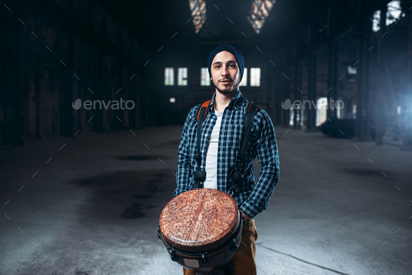 Male drummer playing on wooden drum - Stock Photo - Images