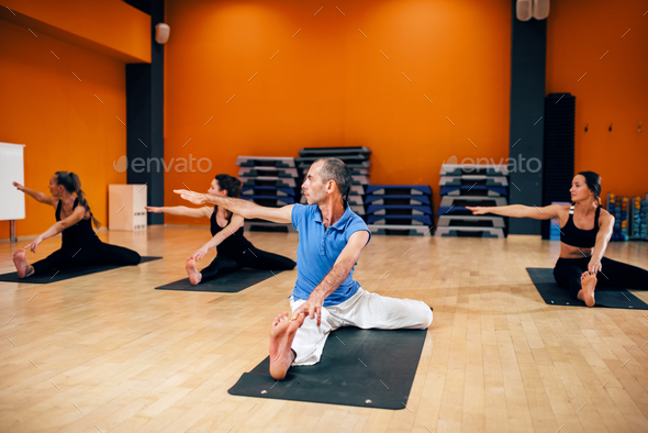 Group with trainer sitting in yoga pose - Stock Photo - Images
