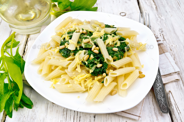Pasta penne with spinach and nuts on board - Stock Photo - Images