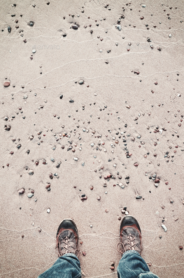Person in hiking shoes stands on a beach. - Stock Photo - Images