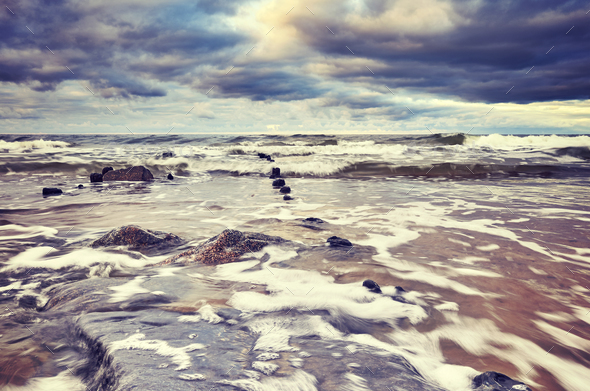 Vintage toned picture of a beach with stormy sky. - Stock Photo - Images