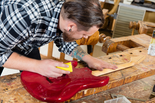 Close-up of craftsman sanding a guitar neck in wood at workshop - Stock Photo - Images