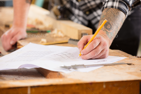 Close-up of carpenter plans project and writes at drawings in workshop - Stock Photo - Images