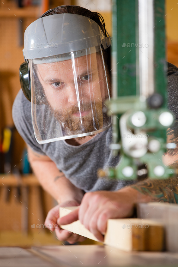 Craftsman with safety mask visor handles band saw in workshop - Stock Photo - Images