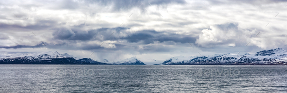 Panorama of clouds over snowy mountains in the arctic - Stock Photo - Images