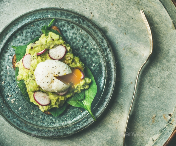 Healthy vegetarian wholegrain avocado toasts with poached egg, top view - Stock Photo - Images