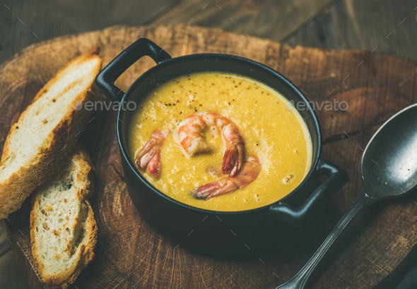Corn creamy soup with shrimps served in pot - Stock Photo - Images