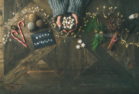 Flat-lay of greeting card, light garland, woman's hands holding mug - Stock Photo - Images