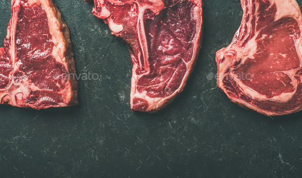 Porterhouse, t-bone and rib-eye steaks over black background - Stock Photo - Images