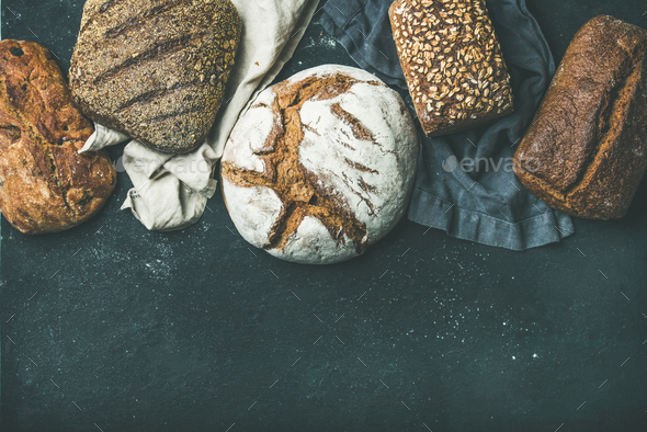 Various bread selection flat-lay, black background, copy space - Stock Photo - Images