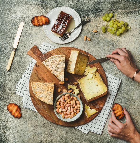 Cheese platter with female hands reaching to food, flat-lay - Stock Photo - Images