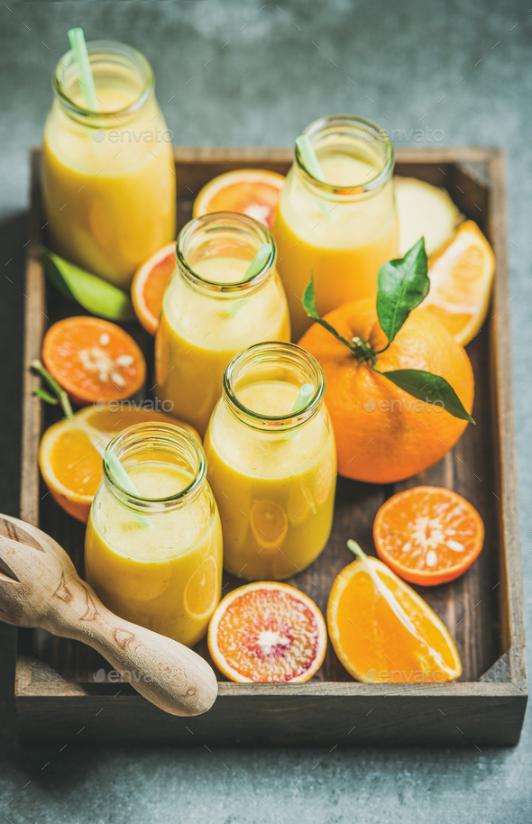 Healthy yellow smoothie in bottles in wooden tray - Stock Photo - Images