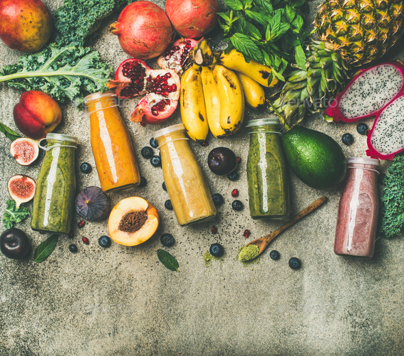 Colorful smoothies in bottles with fresh tropical fruit, copy space - Stock Photo - Images