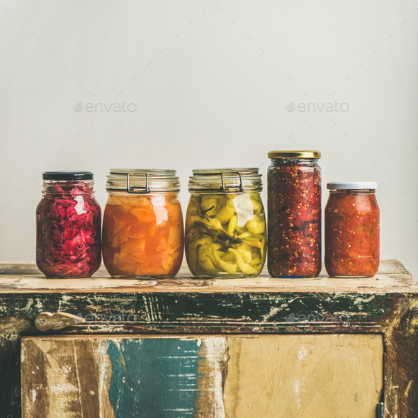 Autumn pickled vegetables in jars placed in line, square crop - Stock Photo - Images