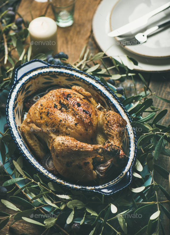 Whole roasted chicken decorated with olive tree branch on table - Stock Photo - Images
