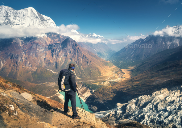 Standing sporty man with backpack on the mountain peak - Stock Photo - Images