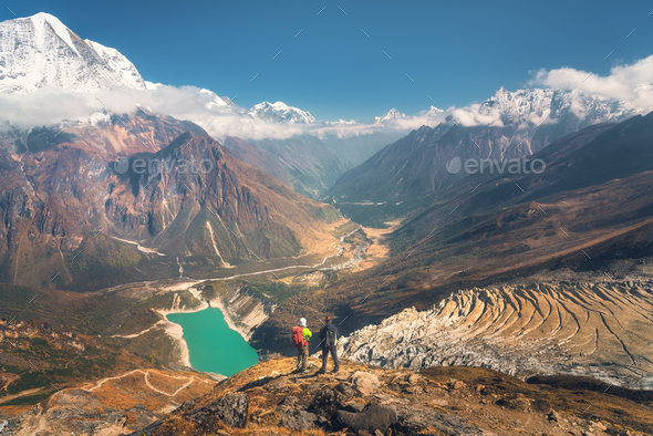 Standing men with backpacks on the mountain peak - Stock Photo - Images