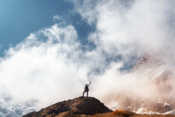 Young woman with raised up arms on the mountain peak - Stock Photo - Images