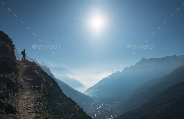 Standing young woman on the hill and looking on mountains - Stock Photo - Images
