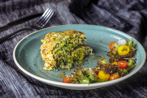 Zucchini Pancakes With salad at blue plate  - Stock Photo - Images
