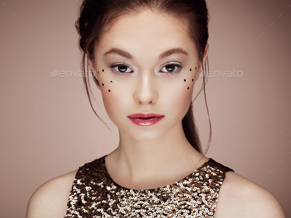Portrait of beautiful young woman in a shiny golden dress - Stock Photo - Images