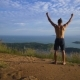 Athletic Young Man Raises His Hands Up Standing on the Edge of the Mountain. - VideoHive Item for Sale