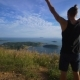 Athletic Young Man Stands with His Hands Up on the Edge of the Mountain. - VideoHive Item for Sale