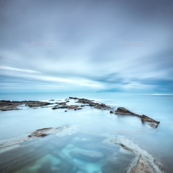 Dark rocks in a blue ocean under cloudy sky in a bad weather. - Stock Photo - Images