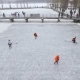 Aerial View of Men Playing Hockey on a Frozen Lake in a City Park in Winter - VideoHive Item for Sale