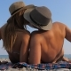 Happy Young Couple Sunbathing On The Beach, Lying On Her Back And Kisses - VideoHive Item for Sale