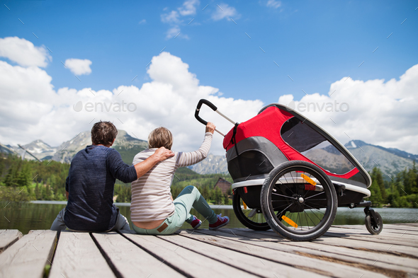 Senior couple with jogging stroller, summer day. - Stock Photo - Images