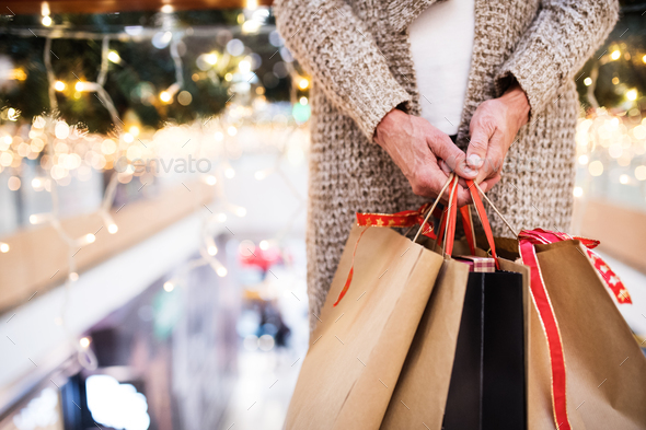 Senior woman with bags doing Christmas shopping. - Stock Photo - Images