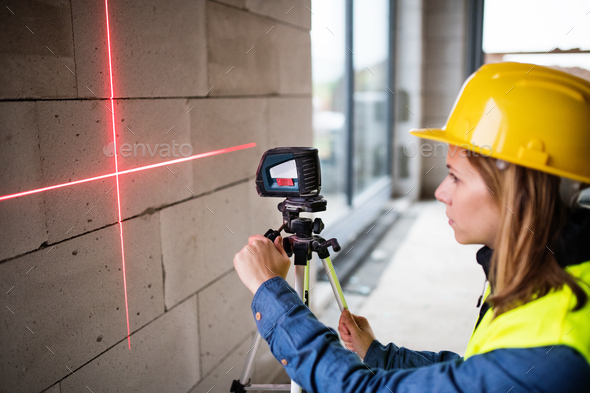 Young woman worker with laser on the building site. - Stock Photo - Images