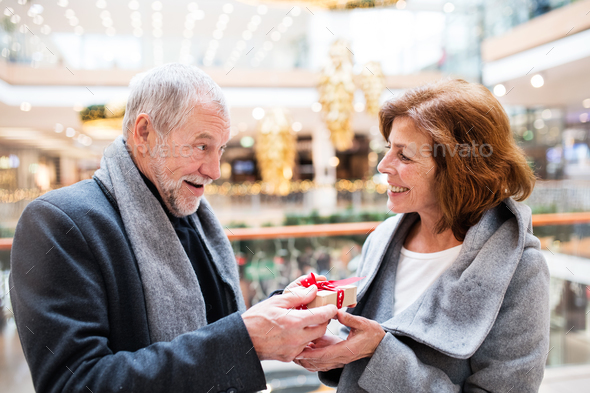 Senior couple with present doing Christmas shopping. - Stock Photo - Images