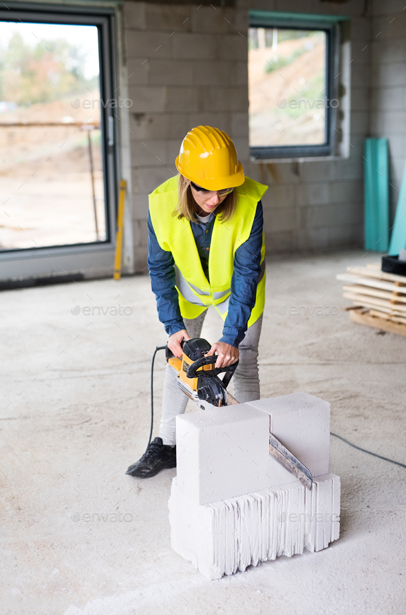 Young woman worker with saw on the construction site. - Stock Photo - Images