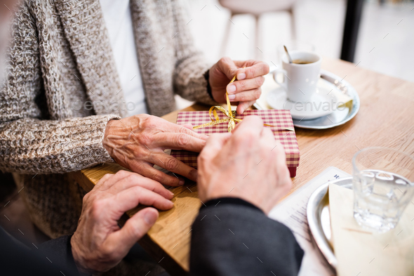 Senior couple with a present in a cafe. Christmas time. - Stock Photo - Images