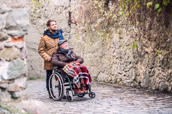 Senior father in wheelchair and son on a walk in old town. - Stock Photo - Images