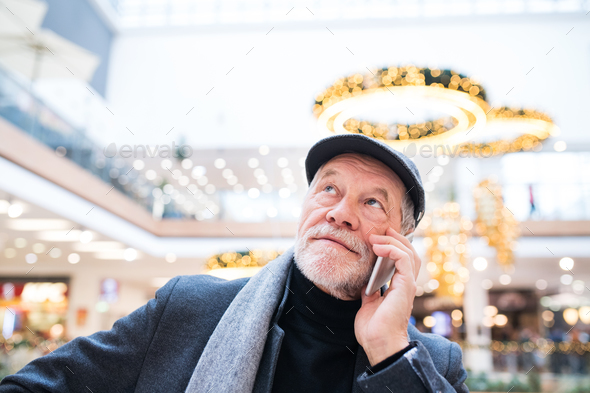 Senior man with smartphone doing Christmas shopping. - Stock Photo - Images