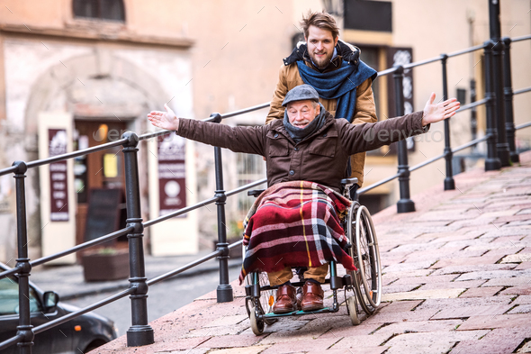 Senior father in wheelchair and young son on a walk. - Stock Photo - Images