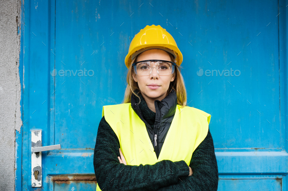 Woman worker standing outside a warehouse. - Stock Photo - Images