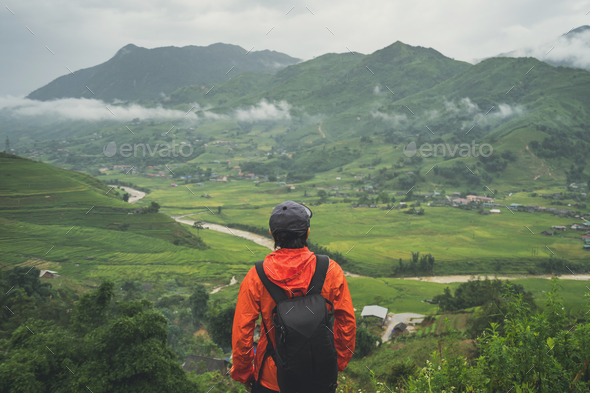 Young traveler standing and looking at view of nature - Stock Photo - Images